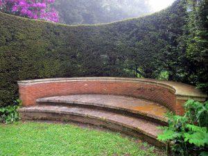 Foto von aus Backsteinen gemauerter, halbrunder Parkbank vor geschnittener grüner Hecke