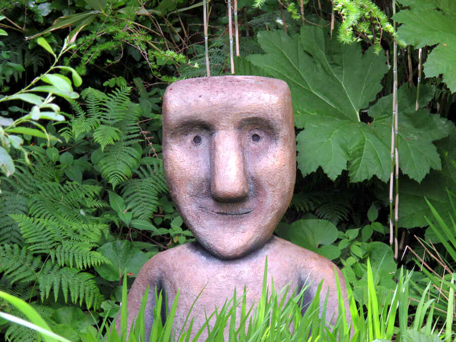Steinfigur mit großem Kopf zwischen Farnen und Blättern.