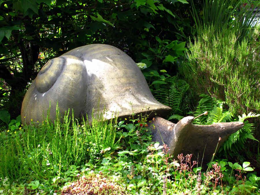 Schnecken-Skulptur zwischen grünen Pflanzen