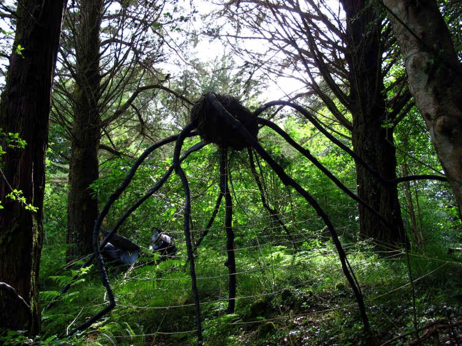 Große Skulptur in Form einer Spinne im Wald zwischen Bäumen.