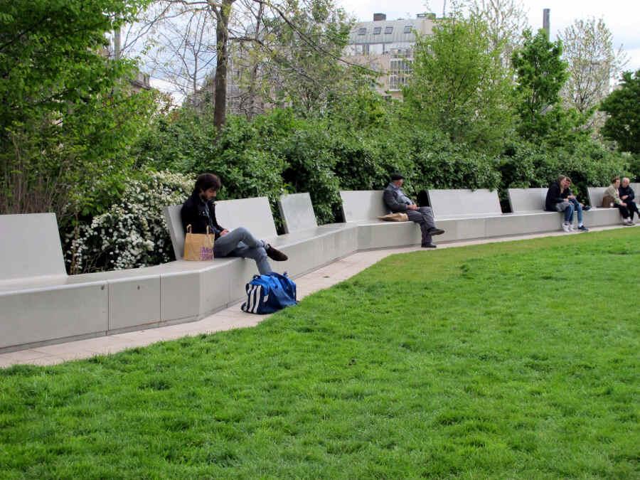 Menschen sitzen auf den modernen Parkbänken im der Jardin Nelson-Mandela in Paris.