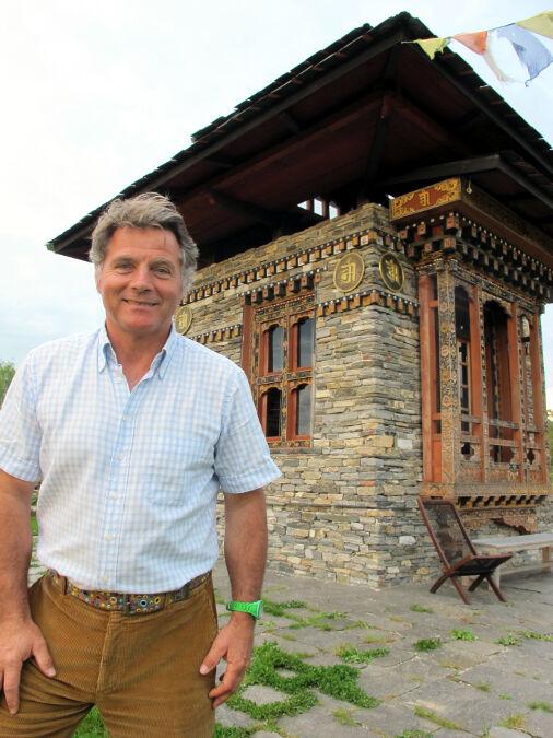 Freiherr Robert von Süsskind steht in seinem Landschaftspark vor einem Tempel aus Bhutan
