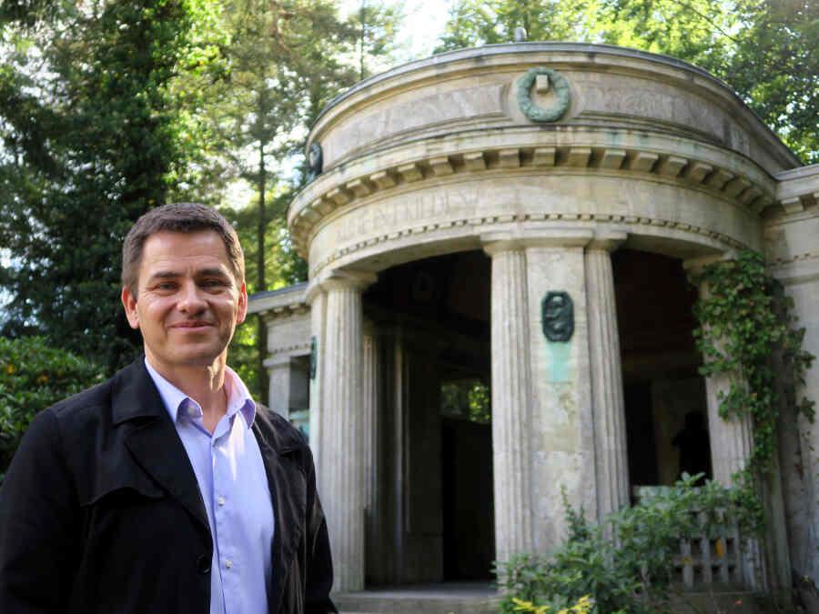 Olaf Ihlefeldt steht vor einem Mausoleum im Waldfriedhof.