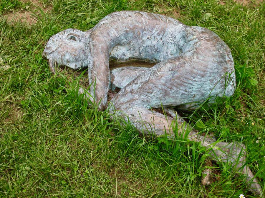 Frauenfigur aus Bronze liegt im Gras im Garten Bois-Guilbert in der Normandie.
