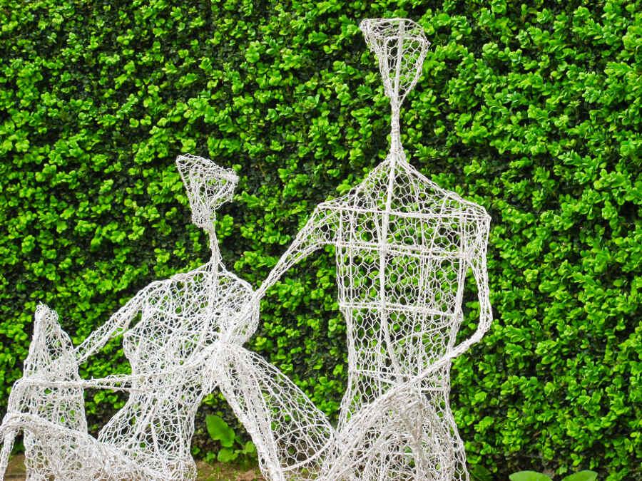 Kunstfiguren aus weißem Draht vor grüner Hecke im Garten Bois-Guilbert in der Normandie.
