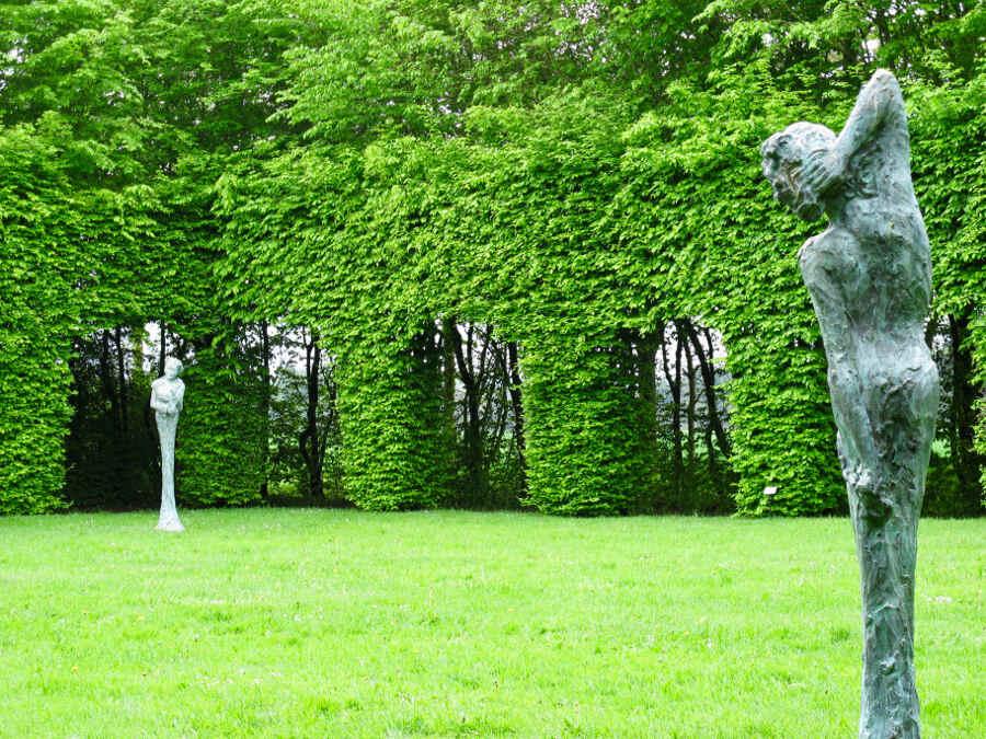Kunstewerke vor einer Hecke im Garten Bois-Guilbert in der Normandie.