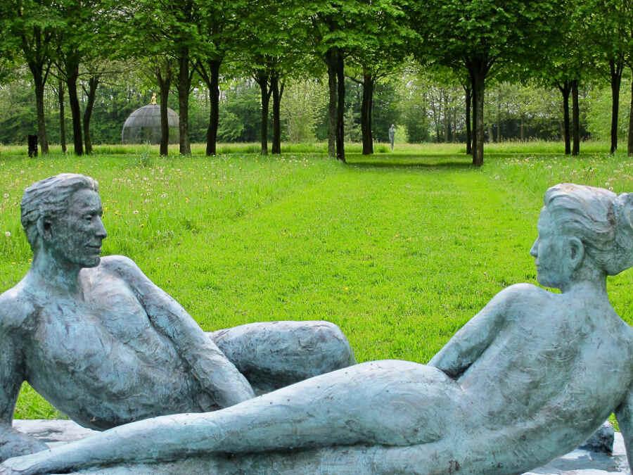 LIebespaar aus Bronze liegt in der Wiese im Garten Bois-Guilbert in der Normandie.